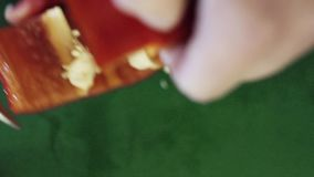 Le plan rapproché du poivre rouge de paprika obtient la coupe avec le couteau sur la table de cuisine verte banque de vidéos