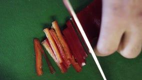 Le plan rapproché du poivre rouge de paprika obtient la coupe pour amincir des rayures avec le couteau sur la table verte banque de vidéos