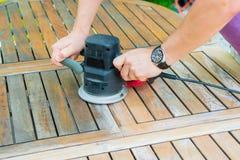 Le plan rapproché du ` s de charpentier remet le travail avec la ponceuse électrique Image libre de droits