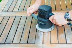 Le plan rapproché du ` s de charpentier remet le travail avec la ponceuse électrique Photos stock