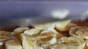 Le plan rapproché du ` s de femme remet la banane de coupe sur le conseil en bois avec le couteau clips vidéos