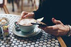 Le plan rapproché du ` s de femme remet tenir le téléphone portable tout en se reposant en café moderne Photos stock