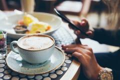 Le plan rapproché du ` s de femme remet tenir le téléphone portable tout en se reposant en café moderne et prenant des petit déje Photo stock