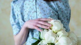 Le plan rapproché du ` s de femmes remet tenir un bouquet des pivoines blanches banque de vidéos
