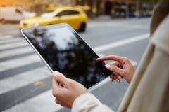 Le plan rapproché du touriste féminin utilise le pavé tactile portatif pour la navigation pendant la marche dans la ville Photos libres de droits