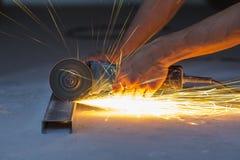 Le plan rapproché du travailleur remet le métal de coupe avec la broyeur Suscite le whil images stock