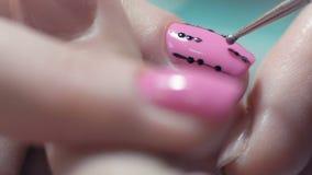 Le plan rapproché extrême, maître de manucure dessine le modèle sur la femme d'ongle dans le salon de beauté banque de vidéos