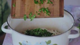 Le plan rapproché extrême, un homme verse le persil coupé en tranches dans un pot avec des ingrédients pour la salade et des émoi banque de vidéos