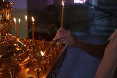 Le plan rapproché femelle de main met l'église par bougie pour la santé Images stock