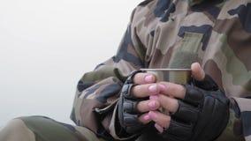 Le plan rapproché, fille dans le costume militaire tient la tasse de fer avec le thé chaud et la boit se reposant le matin brumeu banque de vidéos