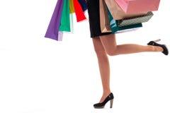 Le plan rapproché inférieur, femme courante tient les sacs en papier et le paquet d'achats Photo libre de droits