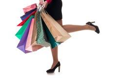 Le plan rapproché inférieur, fille courante tient des sacs en papier et le packa d'achats Image stock