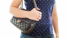 Le plan rapproché a isolé la photo de la jeune femme tenant la main sur le sac à main en cuir noir Photos stock