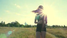 Le plan rapproché, jambes du ` s de femmes dans des espadrilles noires fonctionnent le long du chemin de pré, parmi l'herbe verte clips vidéos