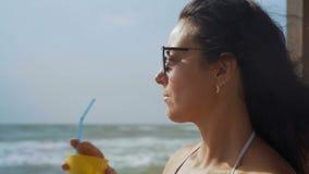 Le plan rapproché, la belle femme dans le maillot de bain blanc et les lunettes de soleil boit le cocktail se reposant sur le bor banque de vidéos