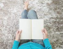 Le plan rapproché la femme qu'asiatique s'asseyant sur le tapis gris au plancher dans la maison a donné au fond une consistance r Photographie stock libre de droits