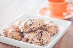 Le plan rapproché a mélangé des biscuits d'écrou à la mini tasse de café orange Images stock