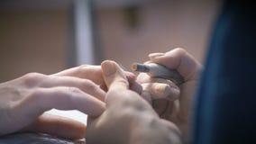 Le plan rapproché, maître de manucure nettoie la couche de laque du doigt de main du ` s de client banque de vidéos
