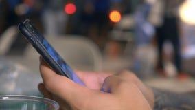 Le plan rapproché, mains d'un jeune hippie masculin introduisent un message textuel au téléphone, brouillant le fond sur une rue  banque de vidéos