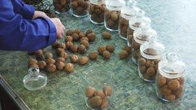 Le plan rapproché, mains du travailleur s a mis des noix dans des pots en verre différentes sortes, développées sélectivement, hy clips vidéos