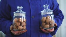 Le plan rapproché, mains du travailleur s tiennent deux pots en verre de la noix, de différentes sortes, cultivée sélectivement,  clips vidéos