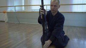 Le plan rapproché, mains posées sur le plancher samouraï sélectionnent le mensonge sur l'épée du ` s de Katana de plancher dans l clips vidéos