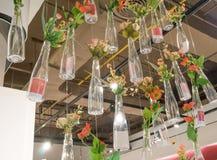 Le plan rapproché a modifié la tonalité la photo des bouteilles décorées avec des fleurs accrochant dessus Images libres de droits
