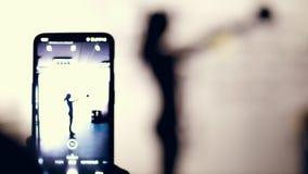 Le plan rapproché, moniteur de smartphone, tirant une figure foncée, contour d'une femme exécute l'exercice avec le poids Femme m banque de vidéos