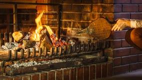 Le plan rapproché remet la cheminée faisant le feu avec des soufflets photos stock