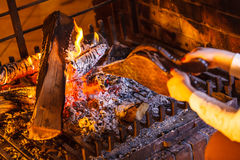 Le plan rapproché remet la cheminée faisant le feu avec des soufflets images stock