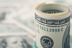 Le plan rapproché a roulé le dollar cent sur le billet d'un dollar américain d'argent de fond Beaucoup billet de banque des USA d Photo libre de droits