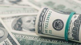 Le plan rapproché a roulé le dollar cent sur le billet d'un dollar américain d'argent de fond Beaucoup billet de banque des USA d Photos libres de droits