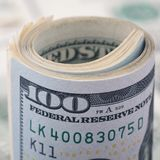 Le plan rapproché a roulé le dollar cent sur le billet d'un dollar américain d'argent de fond Beaucoup billet de banque des USA d Images stock