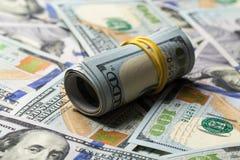 Le plan rapproché a roulé les billets de banque américains des dollars images libres de droits