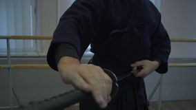 Le plan rapproché, le ` s de samouraïs remet lentement l'insertion dans la feuille d'épée du ` s de katana banque de vidéos