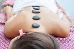 Le plan rapproché sur la jeune femme ayant le massage en pierre chaud soutiennent dessus dans la station thermale photo libre de droits