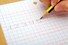 Le plan rapproché sur la main d'une écriture d'enfant numérote Photographie stock libre de droits