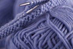 Le plan rapproché sur les boules du fil à tricoter bleu, les aiguilles de tricotage et les boucles tricotées se trouvent sur la t images stock