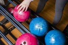 Le plan rapproché sur les enfants de l'adolescence remettent la boule de bowling de participation contre le bowling - image Les e image stock
