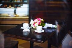 Le plan rapproché tendre de bouquet de mariage se trouve sur une table en bois avec des tasses de café Photographie stock libre de droits