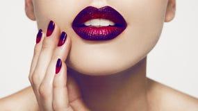 Le plan rapproché a tiré d'une fille appliquant le rouge à lèvres coloré Images libres de droits
