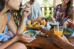 Le plan rapproché tiré des jeunes tout en mangeant le groupe de soupe de nouilles d'amis apprécient la nourriture asiatique tradi Photo libre de droits
