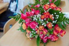 Le plan rapproché a tiré du bouquet rouge des roses, pivoines, grenades Symbole d'amour et de passion Anniversaire ou cadeau d'an Photographie stock