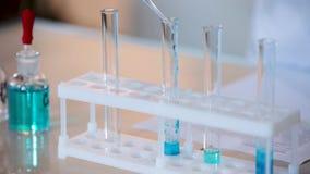 Le plan rapproché a tiré du scientifique s'égouttant le liquide bleu dans le tube à essai Versement du liquide dans le tube de la banque de vidéos