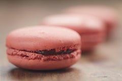 Le plan rapproché a tiré les macarons colorés par pastel avec la saveur de fraise sur la table en bois Photographie stock libre de droits