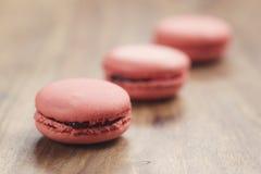 Le plan rapproché a tiré les macarons colorés par pastel avec la saveur de fraise sur la table en bois Photo libre de droits