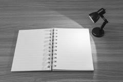 Le plan rapproché un carnet avec la lumière de la petite lampe dans la chambre noire sur le bureau en bois a donné au fond une co Image libre de droits