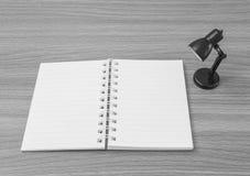 Le plan rapproché un carnet avec la petite lampe dans la chambre sur le bureau en bois a donné au fond une consistance rugueuse d Image stock