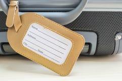 Le plan rapproché une étiquette pour le coup de nom et adresse de suffisance à la valise sur le bureau en bois a donné au fond un images stock