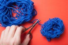 Le plan rapproché, une main femelle coupe une ficelle bleue avec des ciseaux sur un fond rouge image stock